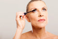 Senior woman putting mascara her eyelashes Royalty Free Stock Photography