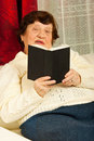 Senior woman reading book home Royalty Free Stock Photos