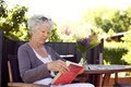 Senior woman reading book relaxed sitting a chair in backyard garden a Stock Images