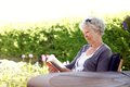 Senior woman reading a book sitting outside on chair at the garden elder novel at her backward garden Royalty Free Stock Photos