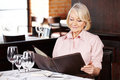 Senior woman reading menu the in a restaurant Stock Photos