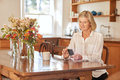 Senior woman reading a message on her phone in kitchen sitting at wooden table tidy rustic text the screen of mobile while Royalty Free Stock Photography