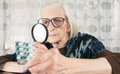 Senior woman reading pill name with magnifying glass Royalty Free Stock Photo