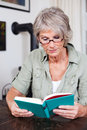 Senior woman reading with reading glasses sitting at a table a book is totally immersed in the story Stock Images