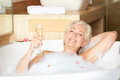 Senior woman relaxing in bath drinking champagne smiling Royalty Free Stock Image