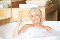 Senior woman relaxing in bath drinking champagne smiling Royalty Free Stock Photography