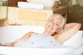 Senior woman relaxing in bath drinking champagne smiling Royalty Free Stock Photo