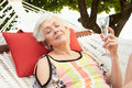 Senior woman relaxing in beach hammock with champagne smiling Royalty Free Stock Photos