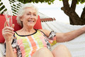 Senior woman relaxing in beach hammock with champagne smiling Royalty Free Stock Photography