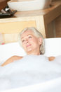 Senior woman relaxing in bubble bath smiling Stock Photo