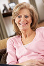 Senior Woman Relaxing In Chair At Home Royalty Free Stock Photos