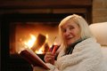 Senior woman relaxing by fireplace happy wrapped in warm knitted plaid at home in the evening sitting in rocking chair drinking Stock Photos