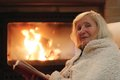 Senior woman relaxing by fireplace happy wrapped in warm knitted plaid at home in the evening sitting in rocking chair and reading Royalty Free Stock Image