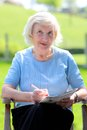 Senior woman relaxing in the garden happy outdoors sitting wooden chair reading newspaper and solving puzzles Royalty Free Stock Photos