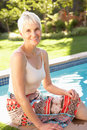 Senior Woman Relaxing By Pool In Garden Royalty Free Stock Photography