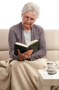 Senior woman relaxing reading a book Royalty Free Stock Photo