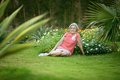 Senior woman at the resort sitting on grass tropic Royalty Free Stock Photo