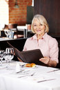 Senior woman in restaurant looking smiling a at the menu Stock Photography