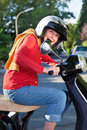 Senior woman riding her scooter crouching low over the handlebars in safety helmet laughing as she rides down the street Stock Photography
