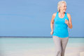 Senior woman running beautiful beach smiling Royalty Free Stock Image