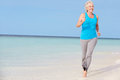 Senior woman running beautiful beach smiling Royalty Free Stock Photos