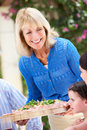 Senior Woman Serving A Family Meal Stock Photography