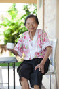 Senior woman seventy years old with good healthy life and a whit white cup of hot water relaxing emotion sitting on desk at home Royalty Free Stock Photos