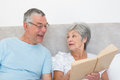 Senior woman showing book to husband in bed women at home Stock Image