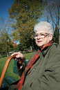 Senior woman sit on a bench Stock Photo