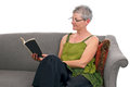 Senior woman sits on sofa and reads book Royalty Free Stock Photos