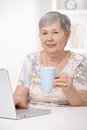 Senior woman sitting at desk using laptop computer drinking tea Royalty Free Stock Images