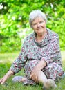 Senior woman sitting on grass in park Stock Photography