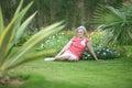 Senior woman sitting on grass at tropic resort Stock Photo