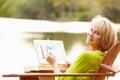 Senior Woman Sitting At Outdoo...