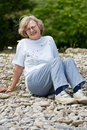 Senior woman sitting on rocky beach Royalty Free Stock Photo