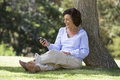 A senior woman sitting under a tree using a mobile telephone Royalty Free Stock Photo