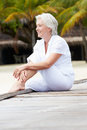 Senior woman sitting on wooden jetty smiling Royalty Free Stock Image