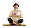 Senior woman sitting in yoga pose on yellow matting isolated on white Stock Image