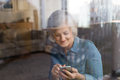 Senior woman with smartphone at home sitting at the window Royalty Free Stock Photo