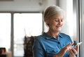 Senior woman with smartphone at home standing at the window Royalty Free Stock Photo