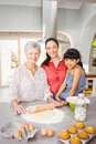Senior woman smiling while preparing food with family portrait of women at home Stock Photos