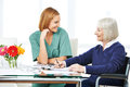 Senior woman solving crossword puzzles smiling women next to nurse in nursing home Stock Photography