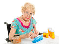 Senior woman sorting pills in wheelchair her weekly medications white background Stock Image