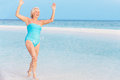 Senior woman splashing in beautiful tropical sea having fun Stock Photography