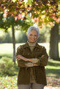 Senior woman standing in autumn garden arms folded smiling front view portrait Royalty Free Stock Photo