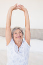 Senior woman stretching on bed smiling in house Royalty Free Stock Images