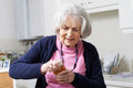 Senior Woman Struggling To Take Lid Off Jar Royalty Free Stock Photo