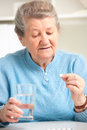 Senior woman taking her medicine close up portrait of an older a Stock Photos