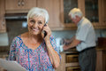 Senior woman talking on mobile phone while man working in kitchen Royalty Free Stock Photo