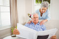 Senior woman talking to senior man reading newspaper Royalty Free Stock Photo